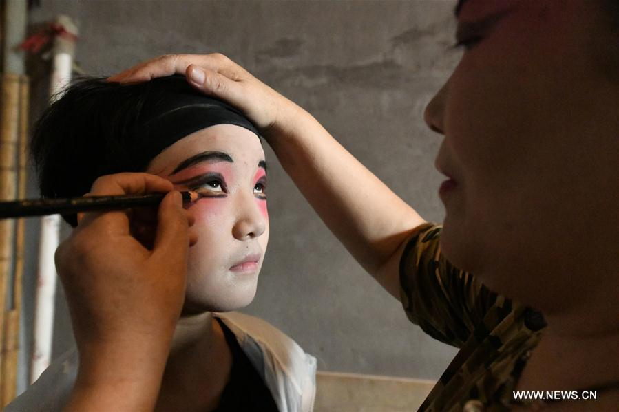 A teacher does facial make-up during an opera class for a student from a primary school in Shijiazhuang, north China\'s Hebei Province, July 18, 2018. Chinese students have entered their summer vacation, during which many of them chose to spend the vacation by developing their hobbies. (Xinhua/Chen Qibao)