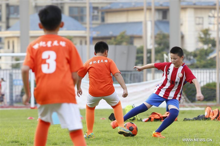 Students attend a football training in Xuyi County of Huai\'an, east China\'s Jiangsu Province, July 18, 2018. Chinese students have entered their summer vacation, during which many of them chose to spend the vacation by developing their hobbies. (Xinhua/Yan Huaifeng)