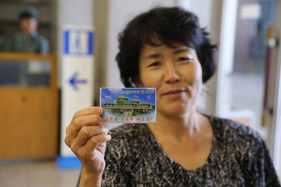 A reader shows her library card to reporters from Xinhua in the Grand People\'s Study House, Pyongyang, DPRK, on July 17, 2018. (Photo/Xinhua)