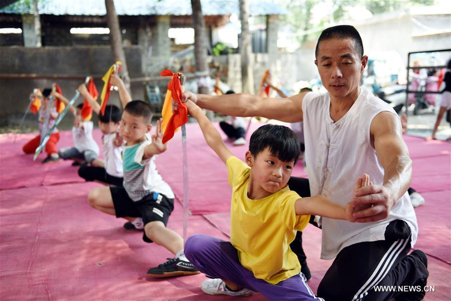 Students learn Chinese martial arts (Wushu) from the trainer Ma Kunpeng in Yancheng County of Linyi City, east China\'s Shandong Province, July 18, 2018. Chinese students have entered their summer vacation, during which many of them chose to spend the vacation by developing their hobbies. (Xinhua/Fang Dehua)