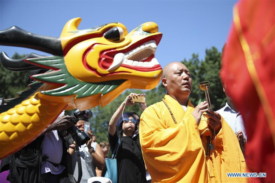 A monk gives blessings during a traditional dragon boat awakening ceremony for the 28th annual Hong Kong Dragon Boat Festival in New York, the United States, on July 18, 2018. The ceremony marked the start of the training period for over 200 teams competing in this year\'s dragon boat races on Aug. 11 and Aug. 12 in New York. (Xinhua/Wang Ying)