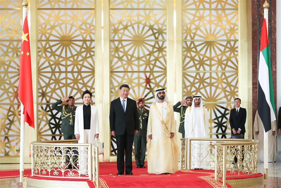 Chinese President Xi Jinping, his wife Peng Liyuan and the United Arab Emirates (UAE) Vice President and Prime Minister Sheikh Mohammed bin Rashid Al Maktoum are seen on a reviewing stand in Abu Dhabi, the UAE, July 19, 2018. Xi arrived here on Thursday for a state visit to the UAE. The UAE\'s vice president hosted a welcome ceremony for the Chinese president at the airport. (Xinhua/Xie Huanchi)