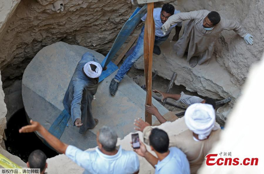 Archaeologists and workers stand over a coffin containing three mummies in Alexandria, Egypt July 19, 2018. (Photo/Agencies)