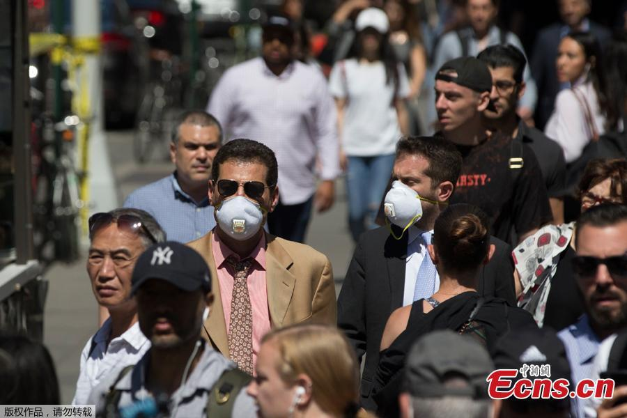 People wear masks after a steam pipe exploded at the Flatiron District in New York City, U.S., July 19, 2018. Five minor injuries have been reported, according to the New York City Fire Department. The incident prompted the evacuation of 28 buildings and warnings of possible asbestos risk. (Photo: China News Service/Liao Pan)