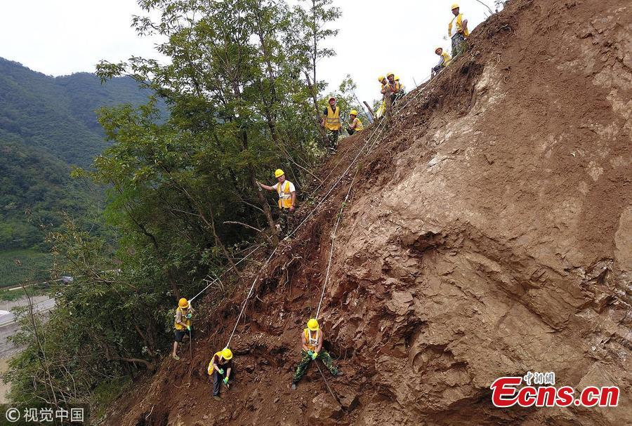 Rescuers clean up a landslide that affected the Baoji-Chengdu Railway after heavy rain in Lueyang County, Northwest China's Gansu Province, July 18, 2018. More than 1,000 people have worked 24 hours to clean up the landslide and resume operations as soon as possible. (Photo/VCG)