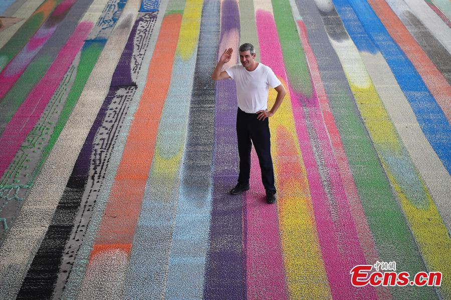 Swiss visual artist Raphael Hefti poses with his creation during an international sculpture festival in Pingyao County, North China's Shanxi Province. More than 40 artists brought their sculpture works to the festival in the ancient town.(Photo: China News Service/Wei Liang)