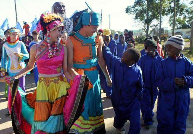 <?php echo strip_tags(addslashes(Members of China's Tianjin Performing Art Troupe take part in a parade with local children in Grahamstown, South Africa on July 9, 2011. (Photo/Xinhua)