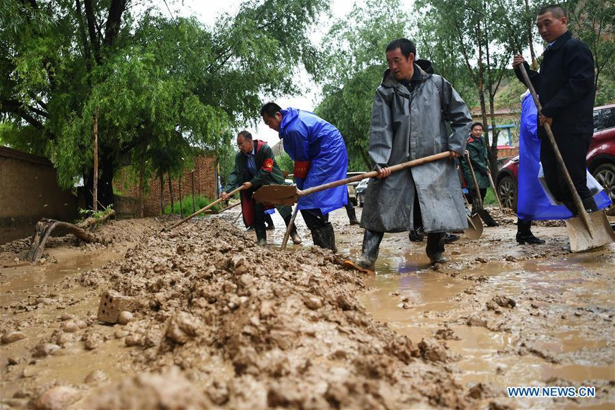 People clear the mud at flood-hit Chenhe Village of Dongxiang Autonomous County in Linxia Hui Autonomous Prefecture, northwest China\'s Gansu Province, July 20, 2018. About 1.08 million people in Gansu Province were affected by rain-triggered floods, with 12 deaths, four people missing and 27,000 people evacuated. (Xinhua/Chen Bin)