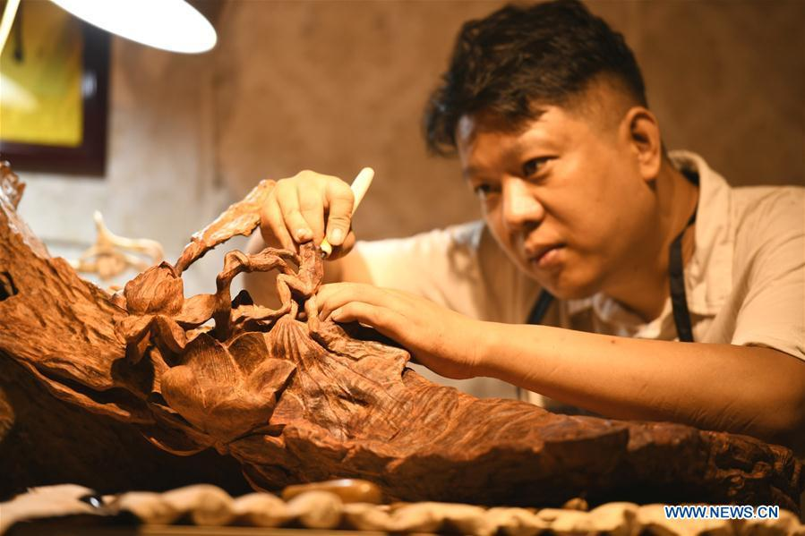 Craftsman Guo Dong makes wood carvings at a studio in Shijiazhuang, capital of north China\'s Hebei Province, July 20, 2018. The \