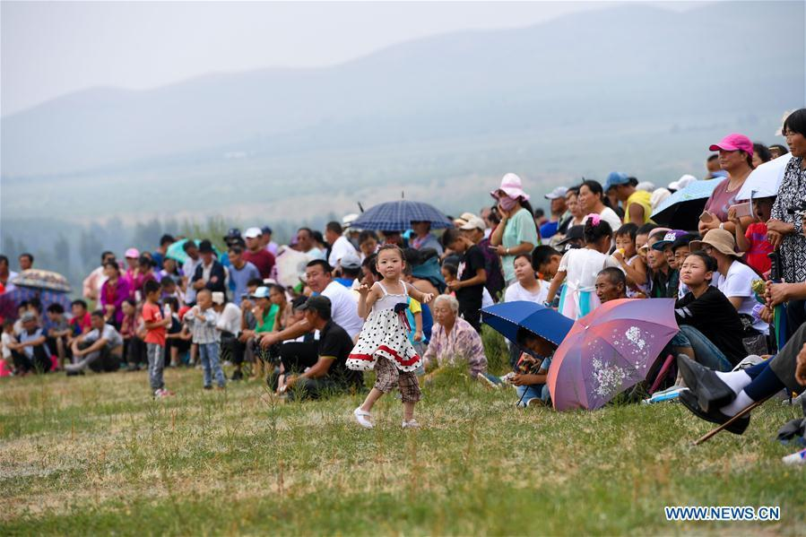 Tourists watch the sports events during a Nadam fair in Chifeng City, north China\'s Inner Mongolia Autonomous Region, July 20, 2018. Nadam Fair, meaning \