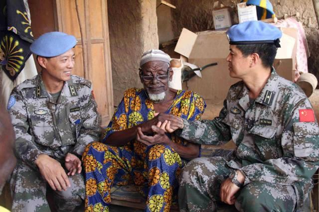 Chinese peacekeepers for the UN Mali Mission chat with an elder after bringing medicines to villagers in Gao, Mali on May 27, 2015. (Photo/Xinhua)