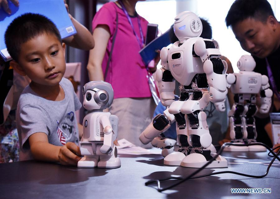Visitors look at robots during the 2018 China International Consumer Electronics Show in Qingdao, east China\'s Shandong Province, July 21, 2018. The four-day electronics show kicked off on Friday. (Xinhua/Li Ziheng)
