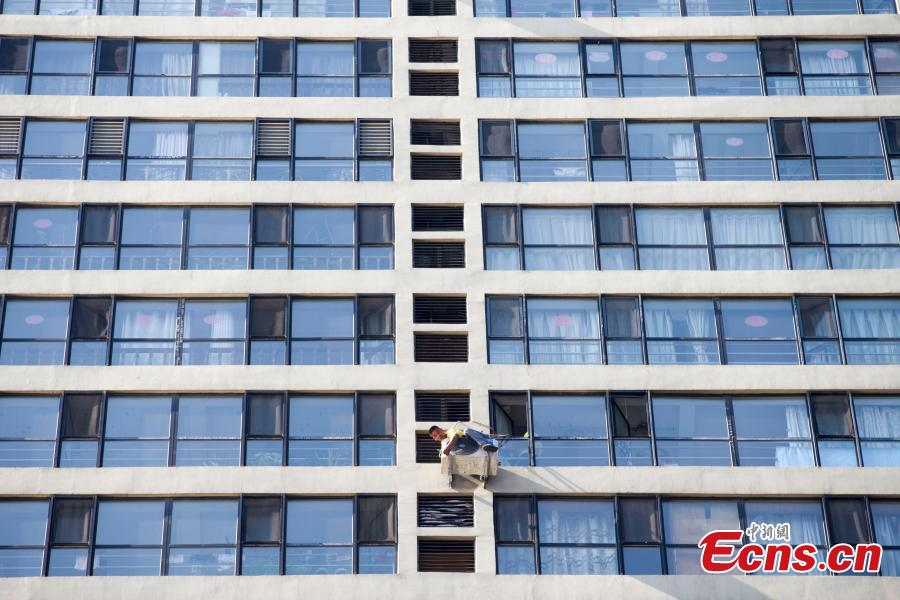 A man, attached to a rope, installs air-conditioning equipment on the outside of a tall building in Taiyuan City, North China's Shanxi Province, July 20, 2018. (Photo: China News Service/Zhang Yun)