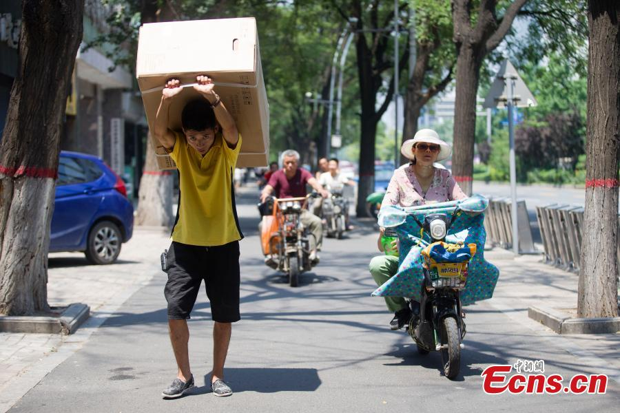 A man carries an air-conditioner in Taiyuan City, North China's Shanxi Province, July 20, 2018. (Photo: China News Service/Zhang Yun)