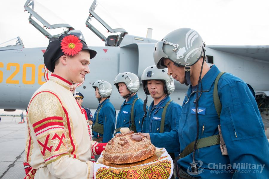 A Russian guy dressed in traditional clothing welcomes the Chinese pilots at the airport on July 20. All aircraft of the PLA Air Force to participate in the \