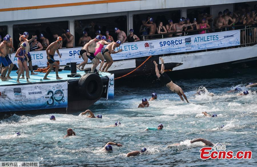 Athletes begin their race from Asia to Europe in the Bosphorus strait during the Bosporus Cross-Continental Swimming Race in Istanbul, July 22, 2018. Over 2,000 open-water competitors plunged into the water from a ferry docked on the city\'s Asian side and swam for about 6.5km in the cross-continental event. (Photo/Agencies)
