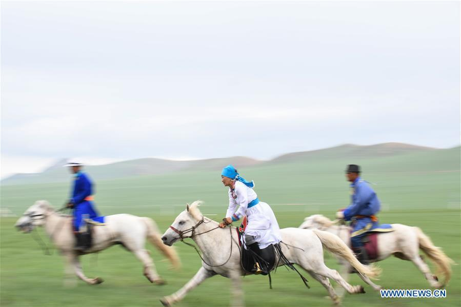 Herdsmen ride horses during a competition celebrating Baima Festival held in West Ujimqin Banner, north China\'s Inner Mongolia Autonomous Region, July 21, 2018. The two-day event is a mass traditional Mongolian festival mainly filled with sports events. (Xinhua/Liu Lei)