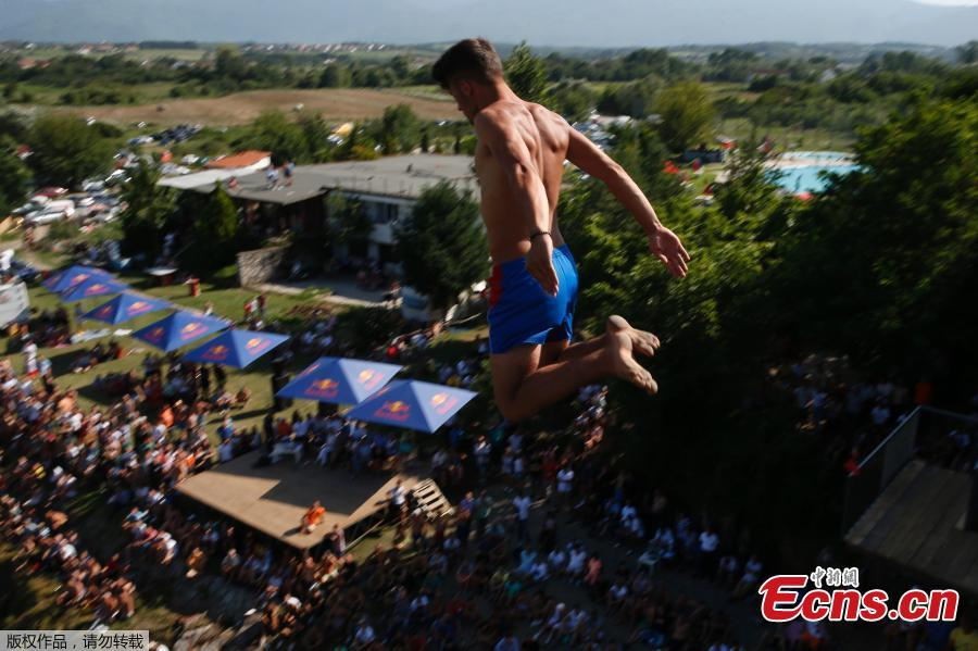 People look at a man as he jumps from the 22 meters high bridge \'Ura e Shenjte\' during the annual traditional High Diving competition near the town of Gjakova on July 22, 2018. (Photo/Agencies)