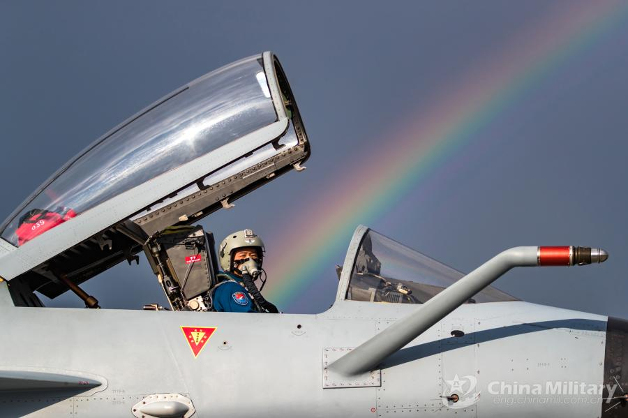 A pilot assigned to the Chinese PLA Air Force sits in the cockpit of his J-10A fighter jet as a rainbow appears in the sky on July 21. All aircraft of the PLA Air Force to participate in the \
