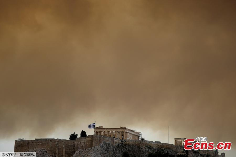 Smoke from a wildfire burning outside Athens is seen over the Parthenon temple atop the Acropolis hill in Athens, Greece, July 23, 2018. At least 20 people died and more than 100 were injured on Monday as a wildfire swept through a small resort town in eastern Greece with many victims trapped by flames as they fled. (Photo/Agencies)