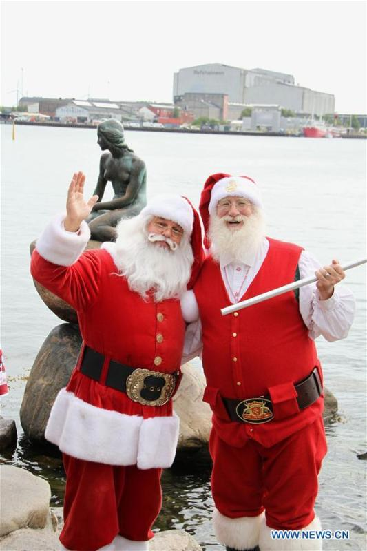 People dressed as Santa Claus pose for photos near the Little Mermaid statue in Copenhagen, capital of Denmark, on July 23, 2018. The 2018 World Santa Claus Congress kicked off at Bakken amusement park, north of Copenhagen, on Monday. Some 100 Santa Claus from around the globe gathered here in the Danish capital city during the four-day event. (Xinhua/Wu Bo)