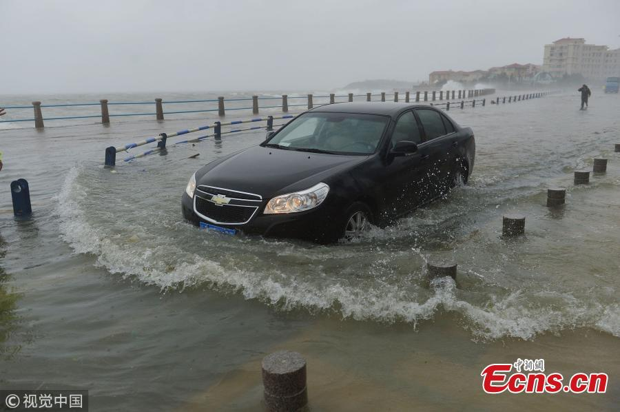 A car struggles through a flooded beach ahead of tropical storm Ampil in Qingdao City, East China's Shandong Province, July 23, 2018. (Photo/VCG)