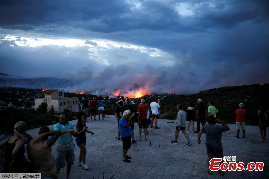 People watch a wildfire raging in the town of Rafina, near Athens, Greece, July 23, 2018. At least 20 people died and more than 100 were injured on Monday as a wildfire swept through a small resort town in eastern Greece with many victims trapped by flames as they fled. (Photo/Agencies)
