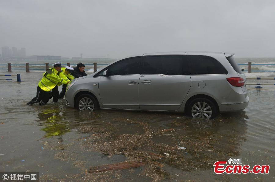 Police officers help move a car stranded in waves on a beach ahead of tropical storm Ampil in Qingdao City, East China's Shandong Province, July 23, 2018. (Photo/VCG)