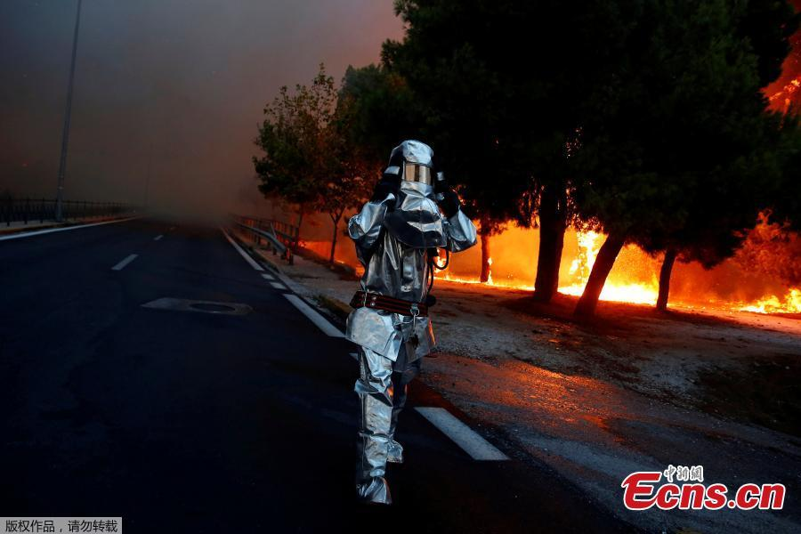 A firefighter wears a flame resistant uniform as wildfire burns in the town of Rafina, near Athens, Greece, July 23, 2018. At least 20 people died and more than 100 were injured on Monday as a wildfire swept through a small resort town in eastern Greece with many victims trapped by flames as they fled. (Photo/Agencies)