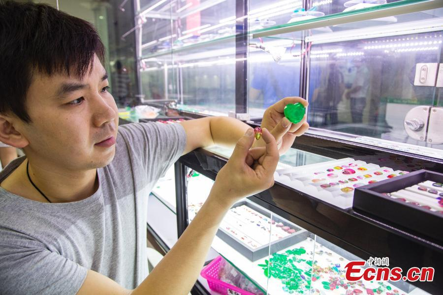 Jian Guoxiong, a gemstone businessman, shows an artificial gem in a jewelry store in Wuzhou City, South China's Guangxi Zhuang Autonomous Region, July 24, 2018. They need to select at least 20,000 qualified pieces from more than 100,000 gemstones a day. Wuzhou is widely held to be the world capital for artificial gems and a trading center that now serves China and the rest of the world. Since the first factory was established there in 1982, Wuzhou now boasts an annual production value for the industry of approximately 3.2 billion yuan ($470 million). (Photo: China News Service/Chen Guanyan)