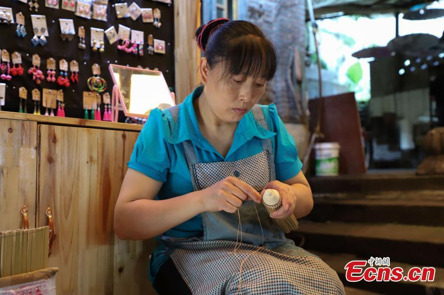 A woman makes an oil-paper umbrella in Datong Ancient Town in Chishui City, Southwest China's Guizhou Province, July 24, 2018. The town has made efforts to creatively develop traditional handicrafts including bamboo weaving and oil-paper umbrella, which help lift locals out of poverty. (Photo: China News Service/Qu Honglun)