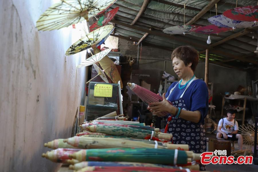 Li Zhenxia, a master at creating oil-paper umbrellas, works in a studio in Datong Ancient Town in Chishui City, Southwest China's Guizhou Province, July 24, 2018. In 2017, Li sold about 10,000 oil-paper umbrellas and earned an income of one million yuan. The town has made efforts to creatively develop traditional handicrafts including bamboo weaving and oil-paper umbrella, which help lift locals out of poverty. (Photo: China News Service/Qu Honglun)
