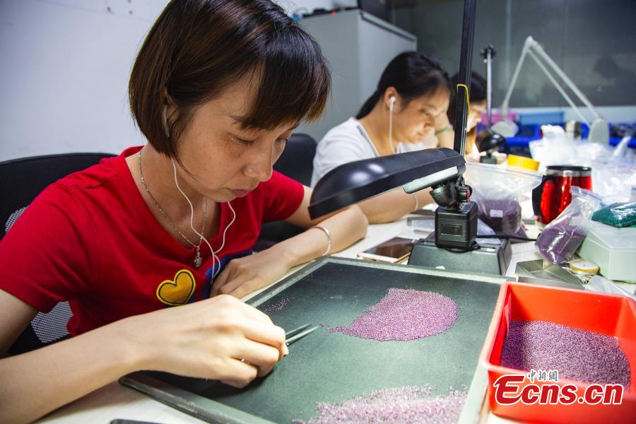 Staff members select gemstones in a jewelry store in Wuzhou City, South China's Guangxi Zhuang Autonomous Region, July 24, 2018. They need to select at least 20,000 qualified pieces from more than 100,000 gemstones a day. Wuzhou is widely held to be the world capital for artificial gems and a trading center that now serves China and the rest of the world. Since the first factory was established there in 1982, Wuzhou now boasts an annual production value for the industry of approximately 3.2 billion yuan ($470 million). (Photo: China News Service/Chen Guanyan)