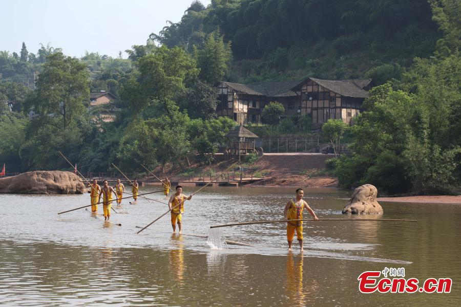 Performers show the single-bamboo pole drifting on water, an intangible cultural heritage, in Datong Ancient Town in Chishui City, Southwest China's Guizhou Province, July 24, 2018. The town has made efforts to creatively develop traditional handicrafts including bamboo weaving and oil-paper umbrella, which help lift locals out of poverty. (Photo: China News Service/Qu Honglun)