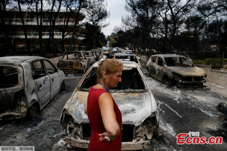 "A local stands next to burnt cars following a wildfire at the village of Mati, near Athens, Greece, July 24, 2018. Greece's prime minister told of the ""unspeakable tragedy"" the country faced after at least 74 people were killed by wildfires that swept through a resort, trapping people in cars and on the edge of cliffs as others were forced to jump off to survive. (Photo/Agencies)"