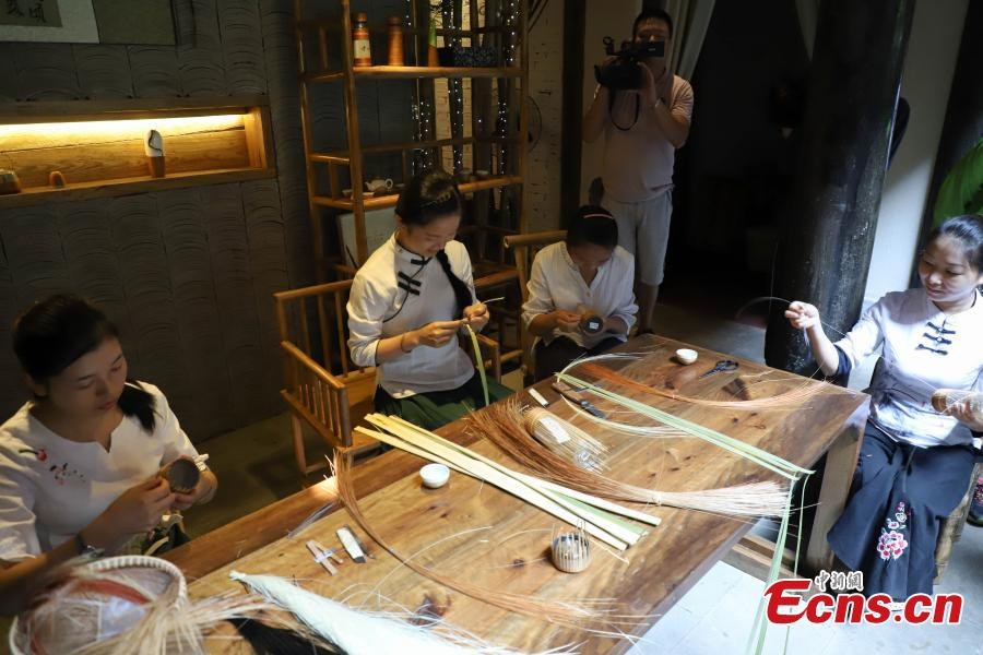 Yang Changqin, a master of bamboo weaving, works in a studio in Datong Ancient Town in Chishui City, Southwest China's Guizhou Province, July 24, 2018. The town has made efforts to creatively develop traditional handicrafts including bamboo weaving and oil-paper umbrella, which help lift locals out of poverty. Yang leads more than 20 local people in a bamboo weaving business, achieving an annual revenue of three million yuan. (Photo: China News Service/Qu Honglun)