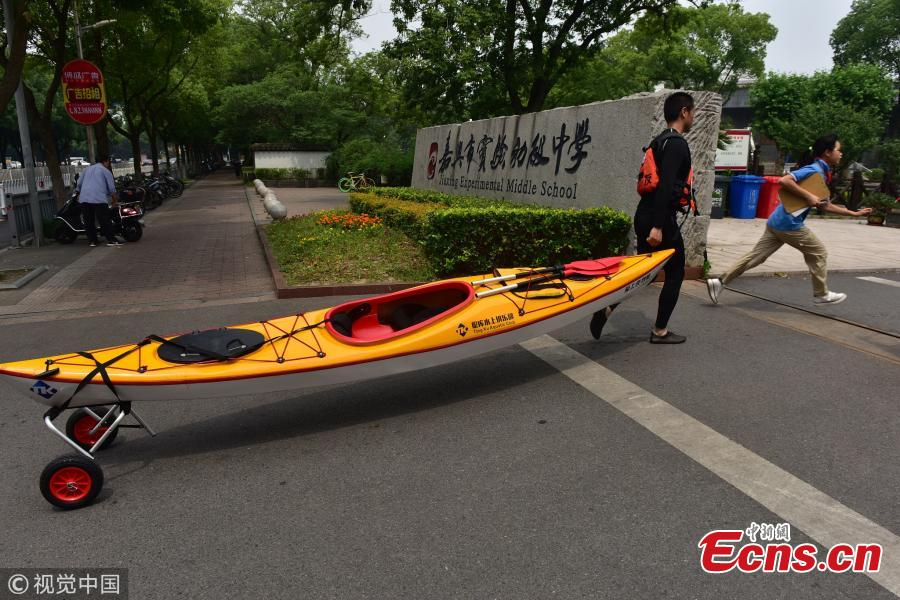 Sports teacher Sun Hua pulls a kayak to a middle school in Jiaxing City, East China's Zhejiang Province. It usually takes him 25 minutes to complete his three-kilometer journey by water. (Photo/VCG)