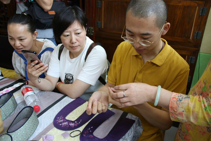 A participant in Great Seed's intangible cultural heritage experience program works on the sole of a shoe, July 21, 2018. (Photo/chinadaily.com.cn)