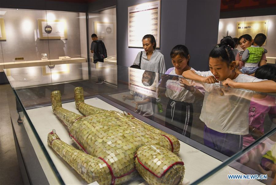 Visitors view a jade clothes sewn with gold wire dating back to the Western Han Dynasty at an exhibition in the Xinjiang Museum in Urumqi, capital of northwest China\'s Xinjiang Uygur Autonomous Region, July 25, 2018. Co-hosted by the Xinjiang Museum and the Xuzhou Museum, the exhibition kicked off on Wednesday. (Xinhua/Hu Huhu)