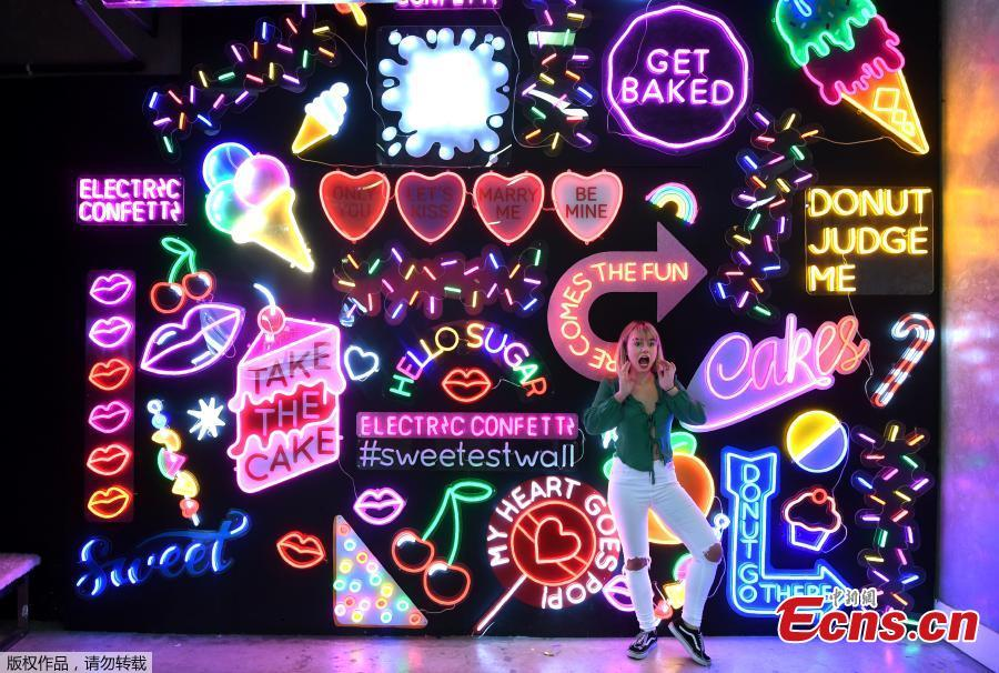 A visitor to Sugar Republic poses in front of a giant wall of neon signs in Melbourne on July 24, 2018. Sugar Republic is an interactive pop-up museum dedicated to the celebration of desserts, candy and all things sweet through 12 amazing sensory rooms.(Photo/Agencies)
