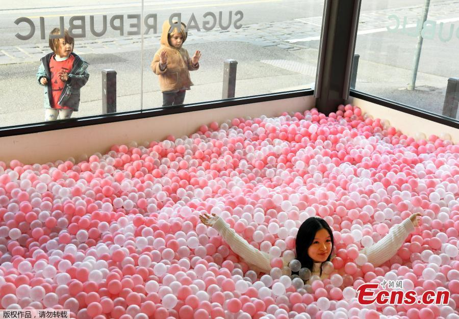 A visitor to Sugar Republic plays in a display of balls resembling lollies in Melbourne on July 24, 2018. Sugar Republic is an interactive pop-up museum dedicated to the celebration of desserts, candy and all things sweet through 12 amazing sensory rooms. (Photo/Agencies)