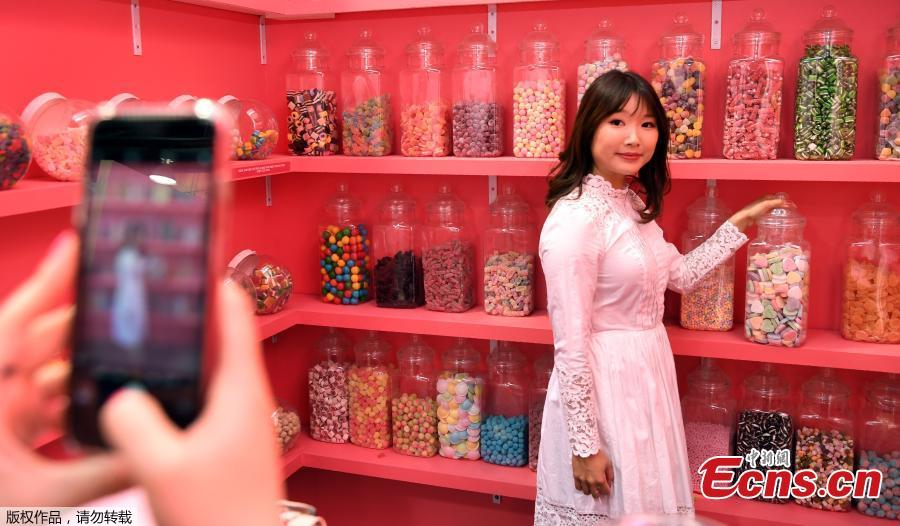 A visitor to Sugar Republic poses for a friend in a display in Melbourne on July 24, 2018. Sugar Republic is an interactive pop-up museum dedicated to the celebration of desserts, candy and all things sweet through 12 amazing sensory rooms.(Photo/Agencies)