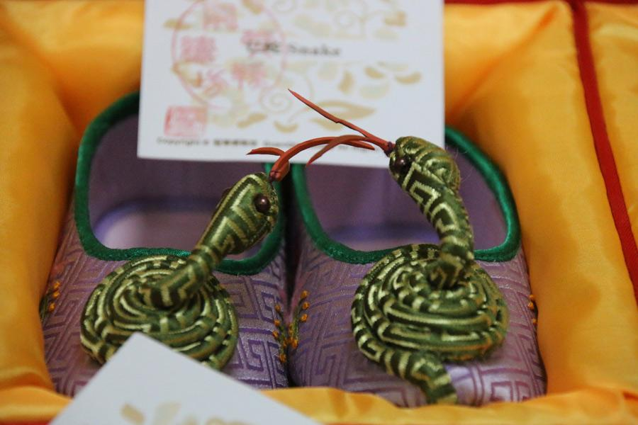 A coiled snake from the Chinese zodiac rises from the toes of a pair of embroidered shoes made by Wang Guanqin, July 21, 2018. (Photo/chinadaily.com.cn)
