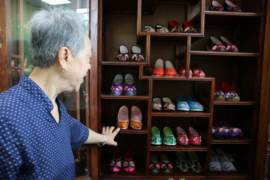 <?php echo strip_tags(addslashes(Wang Guanqin introduces her collection of handcrafted Chinese embroidered shoes to visitors in Beijing on July 21, 2018. (Photo/chinadaily.com.cn)