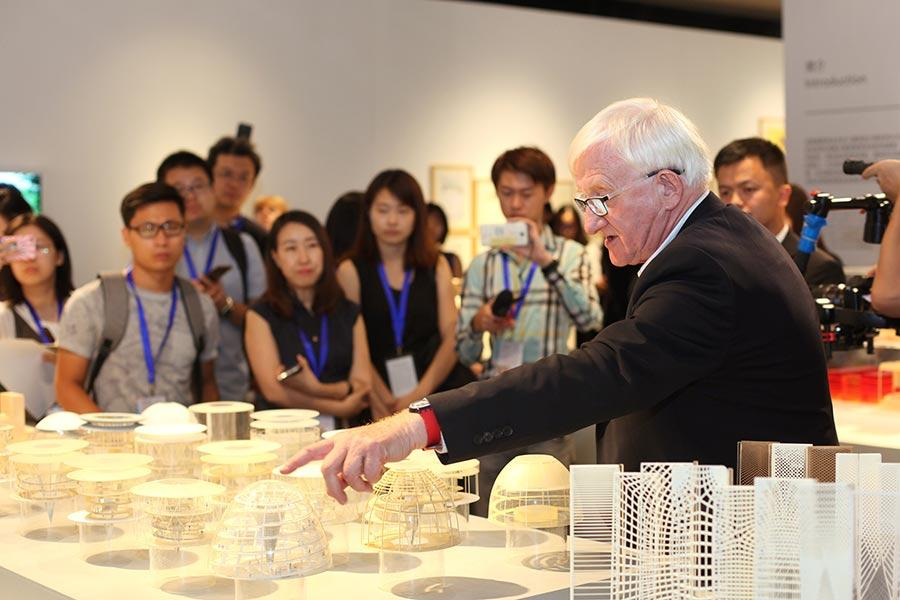 Spencer de Grey, the senior executive partner and head of design at Foster Partners, gives a tour of the exhibition at Tsinghua University Art Museum (Photo provided to China Daily)