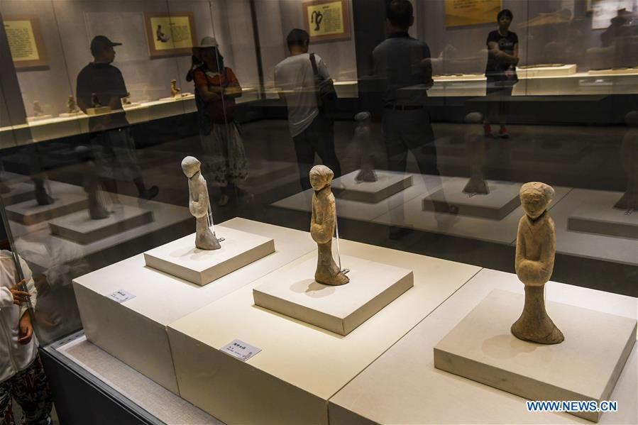 Visitors view pottery figurines dating back to the Western Han Dynasty at an exhibition in the Xinjiang Museum in Urumqi, capital of northwest China\'s Xinjiang Uygur Autonomous Region, July 25, 2018. Co-hosted by the Xinjiang Museum and the Xuzhou Museum, the exhibition kicked off on Wednesday. (Xinhua/Hu Huhu)