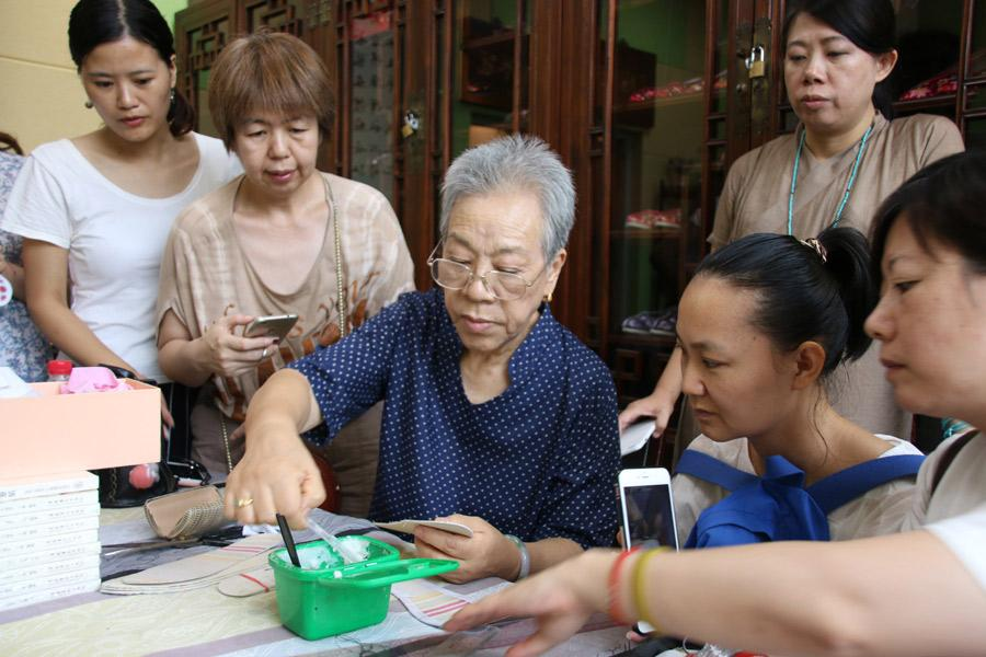 Wang Guanqin guides participants in Great Seed's intangible cultural heritage experience program as they make shoes, July 21, 2018. (Photo/chinadaily.com.cn)