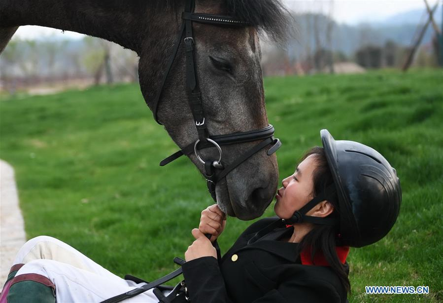 Tang Siqi, a student of Sunshine Riding School, kisses a horse during an outdoor training session in Yihuang County of Fuzhou, east China\'s Jiangxi Province, March 14, 2018. Equestrianism had never been heard of in Yihuang, an agricultural county in east China\'s Jiangxi Province, until Sunshine Riding School began recruiting rural teenagers in 2015. So far, most of the 90 students are working or aspiring to work in horse riding clubs in China\'s largest cities such as Beijing, Shanghai and Hangzhou. (Xinhua/Zhou Mi)