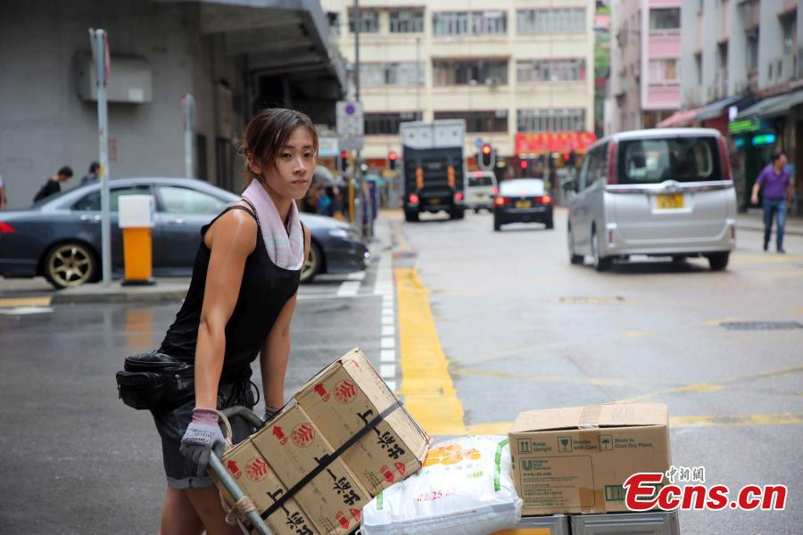 Zhu, a female porter delivers parcels in Ng Fong Street in San Po Kong, Hong Kong, July 13, 2018. Zhu became an internet sensation last year when photos of her working as a porter were shared online. Zhu, 30, transports goods for a local grocery store. She said she has no plan to change her job now. (Photo: China News Service/Hong Shaokui)