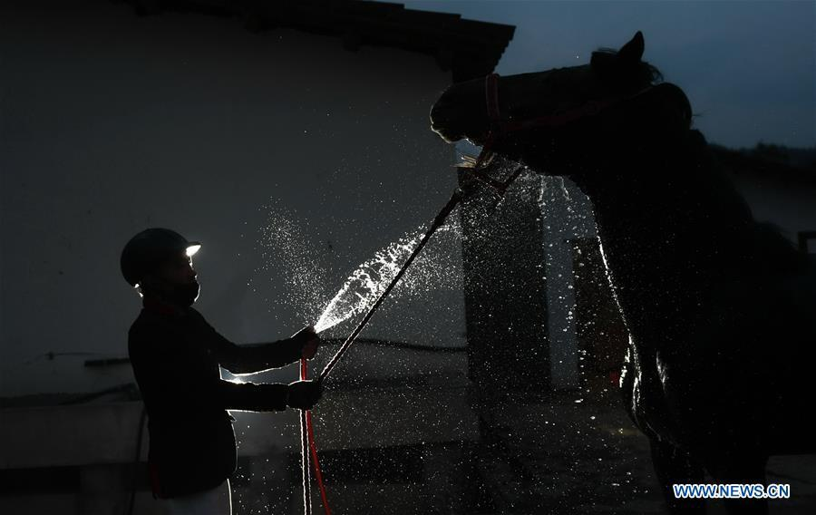 A student of Sunshine Riding School washes a horse after a training session in Yihuang County of Fuzhou, east China\'s Jiangxi Province, March 14, 2018. Equestrianism had never been heard of in Yihuang, an agricultural county in east China\'s Jiangxi Province, until Sunshine Riding School began recruiting rural teenagers in 2015. So far, most of the 90 students are working or aspiring to work in horse riding clubs in China\'s largest cities such as Beijing, Shanghai and Hangzhou. (Xinhua/Zhou Mi)